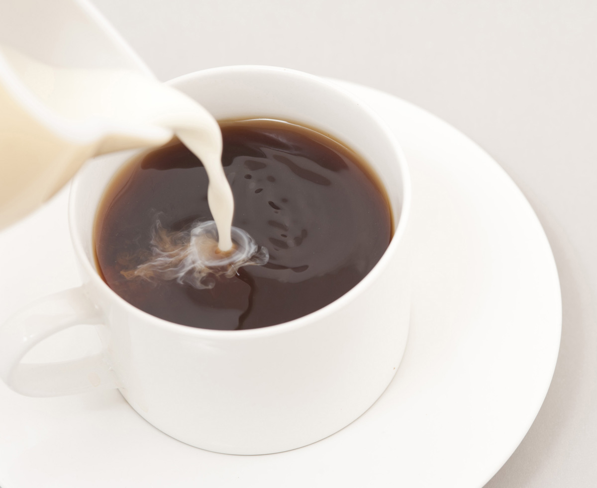 Close up on the spout of a milk jug pouring milk into a cup of black coffee in a generic white cup and saucer